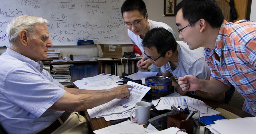 John B. Goodenough, professor in the Cockrell School of Engineering at The University of Texas at Austin, works with students in his office