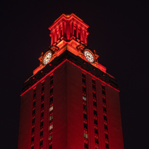 the UT Tower shines with burnt orange lights at night.