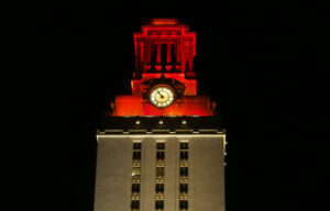 The top of the UT Tower shines with burnt orange lights.