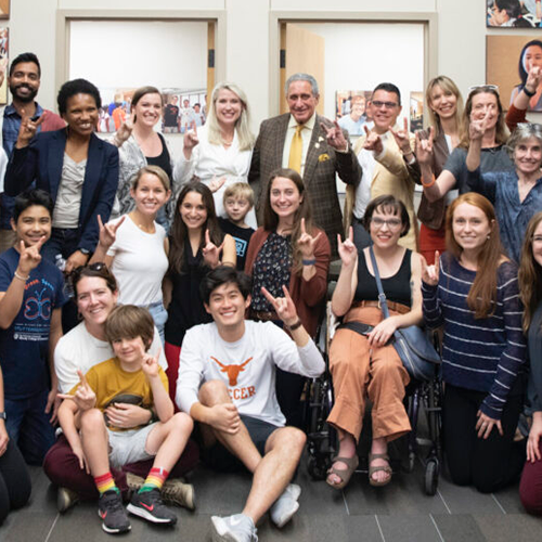 A group of people poses for a picture while showing their Hook Em Horns hand signs.