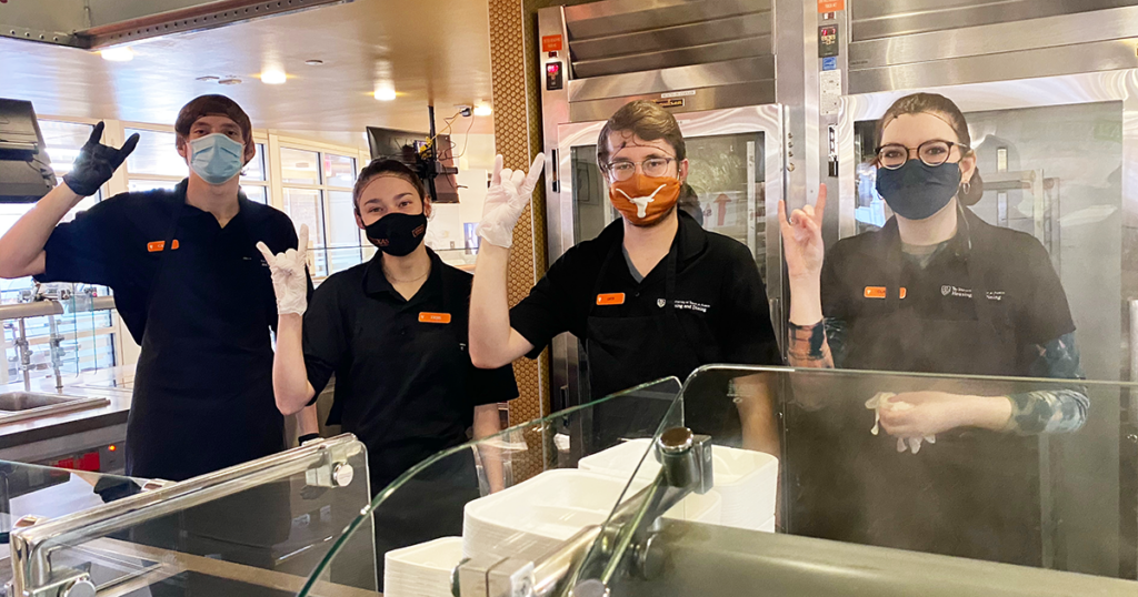 UT Dining employees pose for a picture while showing the Hook Em Horns hand sign.