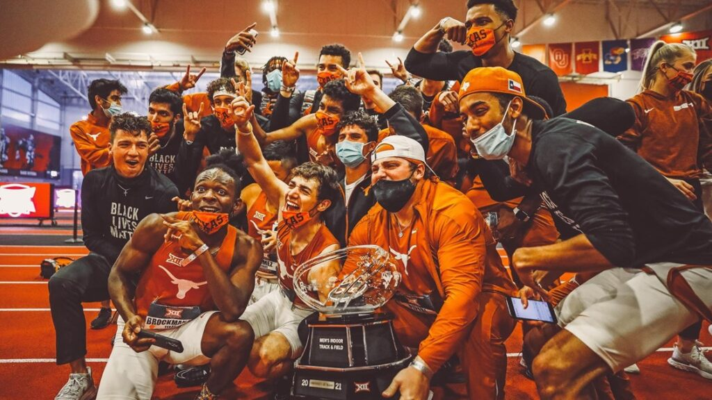 Members of the Men's Track and Field team gather around a trophy in celebration
