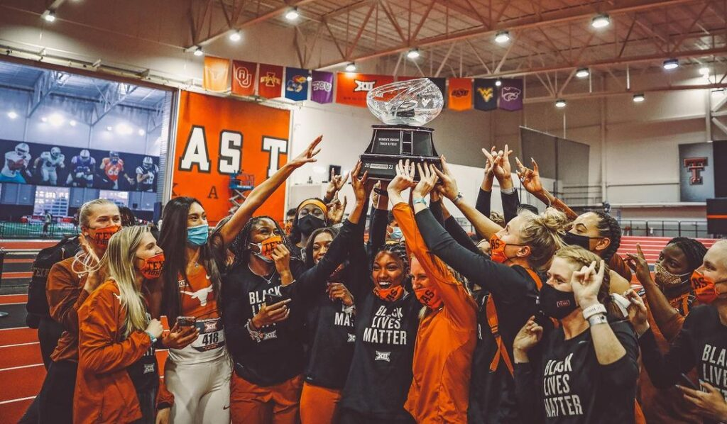 Members of the Women's Track and Field team hold up a trophy in celebration