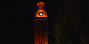 The UT Tower shines with burnt orange lights in front of a dark night sky.