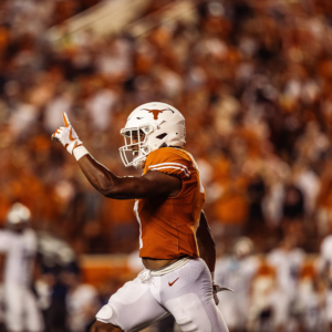 A Texas Football player runs down the field and points his finger in the air in celebration.