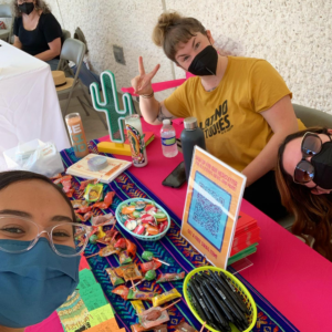 Three people gather around a table while promoting Latino Studies